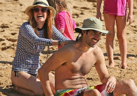 Isla Fisher with her husband on a beach